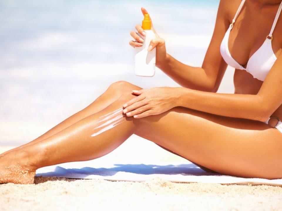 chica poniéndose crema protectora en la playa